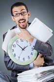Homme avec horloge et des tas de papiers — Photo