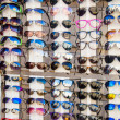 Many sunglasses on display in shop - Stock Photo