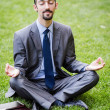 Young businessman meditating in the garden — Stock Photo