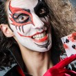Evil clown with cards in dark room - Foto Stock