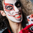 Evil clown with cards in dark room - Stock Photo