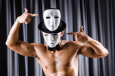 Muscular actor with mask against curtain — Stock Photo
