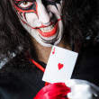 Evil clown with cards in dark room - Stockfoto
