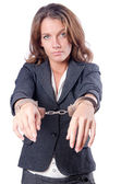 Female businesswoman with handcuffs on white — Stock Photo