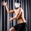 Muscular actor with mask against curtain - Stock Photo