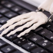 Skeleton working on the keyboard - Stock Photo