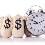 Sacks of money and alarm clock on white — Stock Photo #24052443