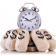 Sacks of money and alarm clock on white — Photo