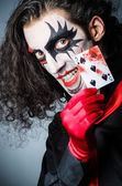 Evil clown with cards in dark room — Stock Photo