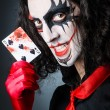 Royalty-Free Stock Photo: Evil clown with cards in dark room