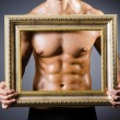 Muscular man with picture frame — Stock Photo #24920359