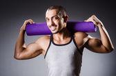 Muscular man with mat in studio — Stockfoto