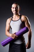 Hombre musculoso con estera en estudio — Foto de Stock