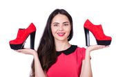 Young woman with choice of shoes on white — Stock Photo