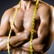 Muscular man measuring his muscles - Stock Photo