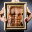 Muscular man with picture frame - Stock Photo