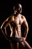 Muscular man in dark studio — Stock Photo