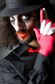Joker personification with man in dark room — Stock Photo