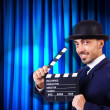 Man with movie clapper on curtain background — Foto Stock