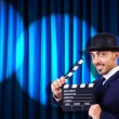 Man with movie clapper on curtain background — Stock Photo