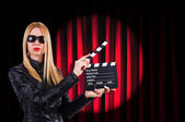 Girl with movie board against curtains — Stock Photo
