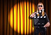 Flicka med film styrelsen mot gardiner — Stockfoto