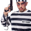 Badly bruised prisoner with gun — Stock Photo #30887801