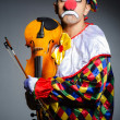 Sad clown performing at vioin — Stock Photo