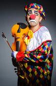Sad clown performing at vioin — Stock Photo