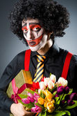 Sad clown with the flowers — Stock Photo