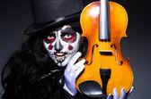 Monster playing violin in dark room — Stock Photo