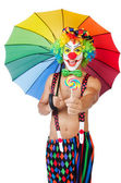 Clown with umbrella and lollypop — Stock Photo