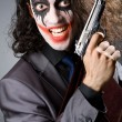 Joker with gun and briefcase — Stok fotoğraf