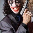 Joker with gun and briefcase — Stockfoto