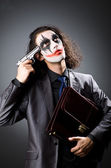 Joker with gun and briefcase — Stock Photo