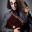 Stock Photo: Joker with gun and briefcase
