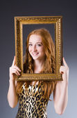Redhead with picture frame against dark background — Stok fotoğraf