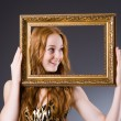 Redhead with picture frame against dark background — Stock Photo