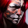 Woman with face painting in dark room — Stock Photo