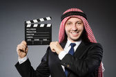 Arab man with movie clapper — Stock Photo