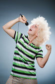 Man in afro wig singing with mic — Stock Photo