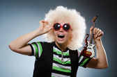 Funny man with miniature guitar — Stock Photo