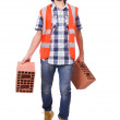 Builder with clay bricks — Stock Photo