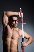Man with sword and face paint — Stock Photo
