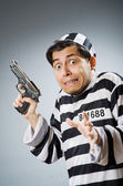 Prisoner with gun against dark background — Stock Photo