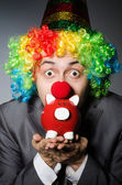 Clown with piggybank in funny concept — Stock Photo