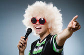 Man in afrowig singing with mic — Stock Photo