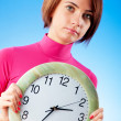 Young woman holding round clock in the hands — Stock Photo #5134929