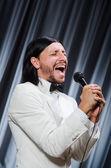 Man zingen voor gordijn in karaoke concept — Stockfoto