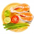 Two raw salmon steaks with tomatoes, lime  and green onion on  — Stock Photo